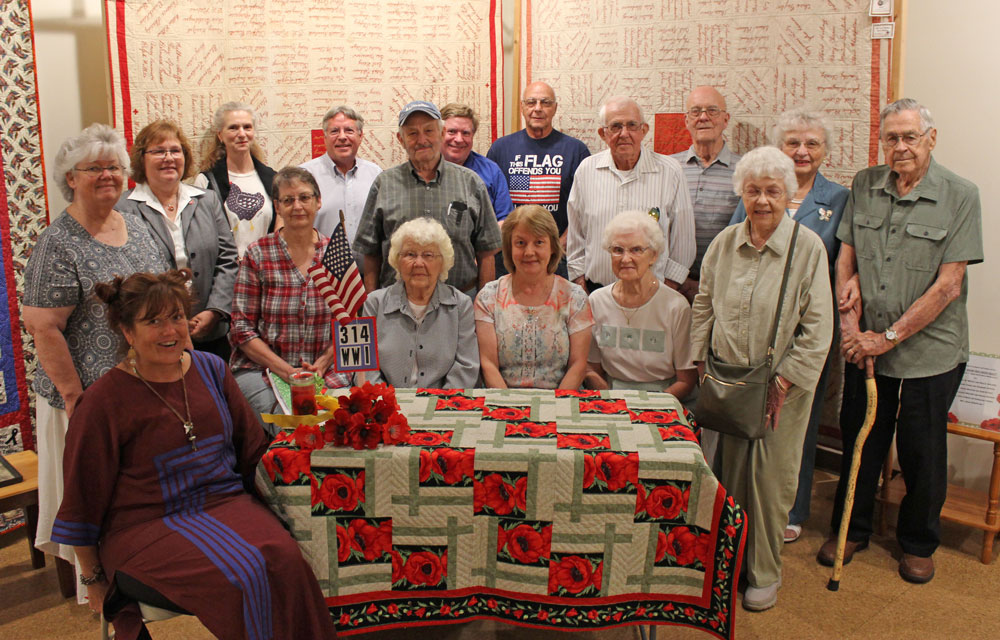 CAP: Relatives representing 314th soldiers at the July 15, 2018 gathering at the LCHS/Thomas T. Taber Museum were (Front): Krys Yarish, relative of John Shetler, Danville, Ralph Lyons, Millville, E. Frank Gardner, Unityville; Kay Bitner relative of William K. Campbell and Samuel English, Jersey Shore; Frances Bigger and daughter Susan Smith, niece and grandniece of E. Frank Gardner of Unityville; Helen Meyer, daughter of Harold Lauchle of Huntersville; Mary Ann Williams, daughter of Homer M. Rood of Morris Run. (Row 2): Carol Shetler, relative of the aforesaid Lyons and Gardner; program speaker Nancy Schaff, granddaughter of John Blazosky of Port Matilda; Patty Lane, granddaughter of James Lane of Dushore; William Nicholson, grandson of Evan Rosser, Williamsport, William Olson, son of Carl Olson of Duboistown; Thomas Nicholson, grandson of aforesaid Rosser; Don Baylor, nephew of Ralph Baylor of Mooresburg; Leigh Rood, son of Homer Rood, Morris Run; Ray Confer, son of Raymond Confer of Muncy; Evelyn Seaman, daughter of Otto Hess of Morris; and Paul Seaman, nephew of Samuel Seaman of Bradford.