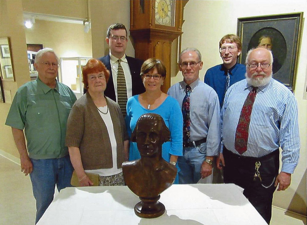 Museum Board member Eiderson Dean, widow of the carver Jane Landon, son of the carver Ben Landon, donor Susan G.S. Anderson, donor Dan Llewellyn, Curator Scott Sagar, and Museum Director Gary Parks.
